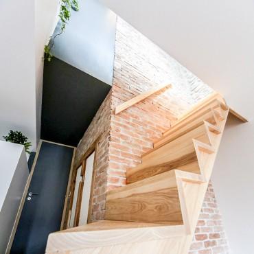 deux escaliers en un, bois et mur en briques